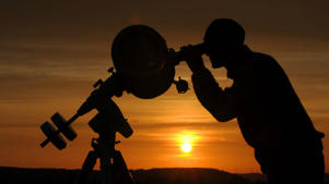 a man with dark hair and a sunset in the background: space_telescope_venus