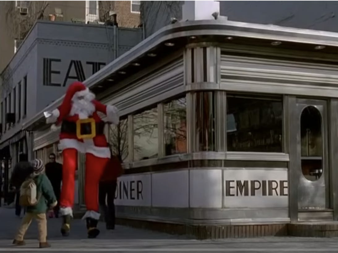 Slide 11 of 36: The scene, which is only a couple of seconds long, features McCallister crossing paths with a Santa on stilts outside of Empire Diner.