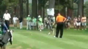 a group of people walking in the grass: Charles Barkley's playing golf