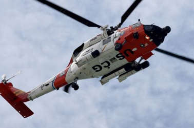 a helicopter flying in the air: Coast Guard helicopter