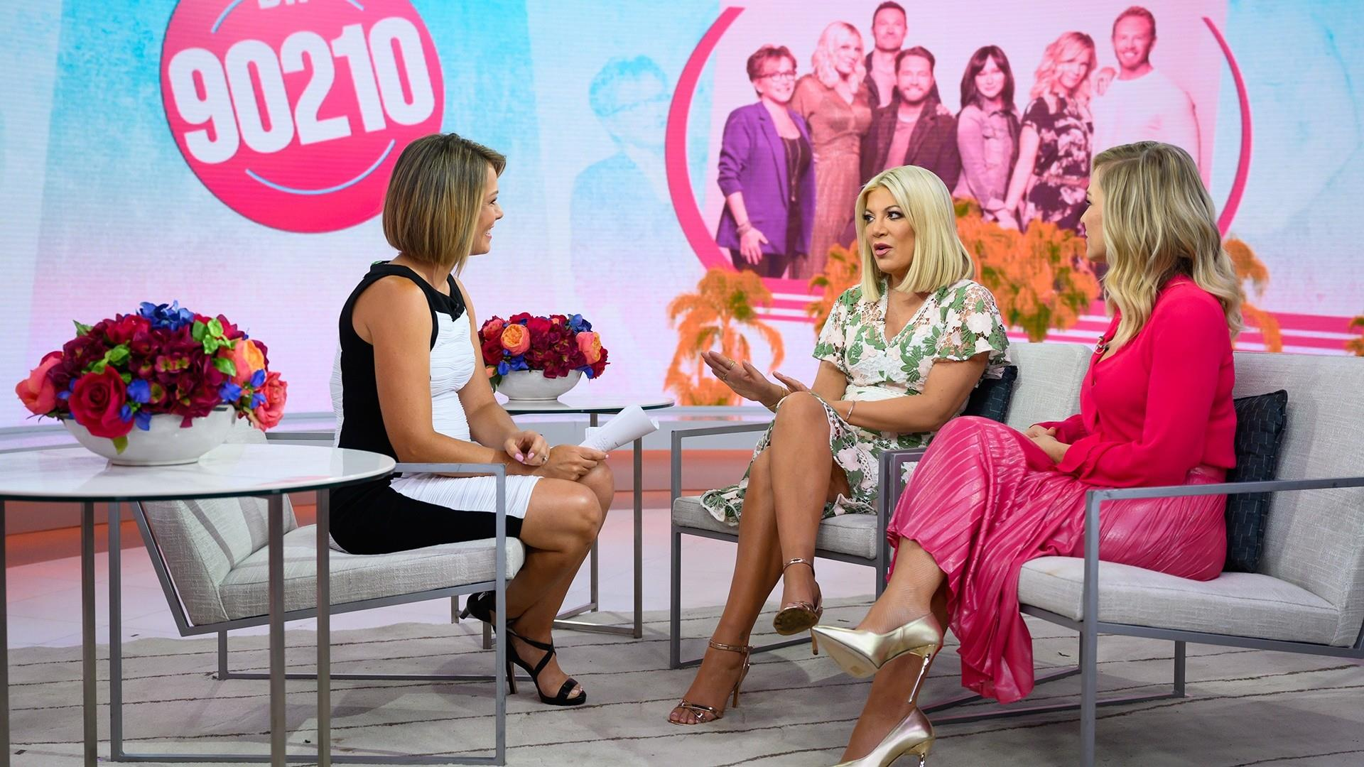 "a man and a woman sitting on a bench: ""Beverly Hills, 90210"" stars Tori Spelling and Jennie chat with Dylan Dreyer about the highly anticipated reboot of the show, ""BH90210."" They also open up about the recent death of their co-star, Luke Perry. ""In a weird universal way, it was a way for us to be together during an incomprehensible painful time,"" Garth says. ""He was with us every second."""