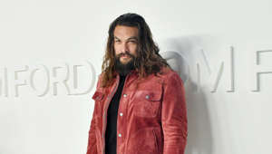 Jason Momoa standing in front of a coat