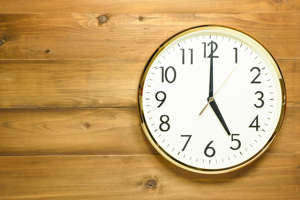 a clock sitting on top of a wooden table: 5 at 5: Your Daily Digest for Real Estate Investing, 2/9/21