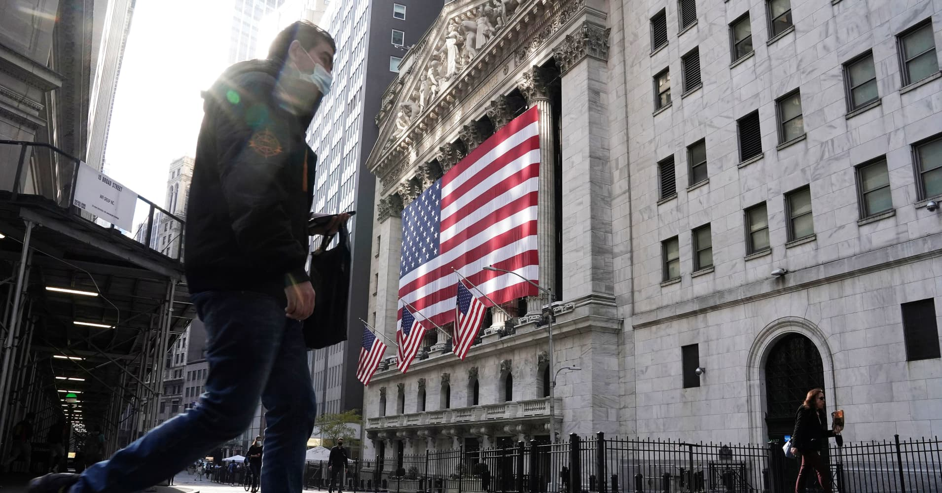 a man standing in front of a building: U.S. stock index futures edged lower for the last trading day of November, as Wall Street prepared to trim historic gains made in the month.