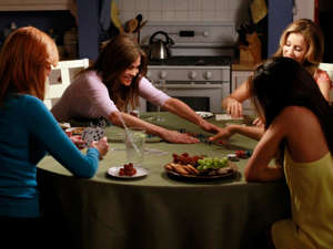 a group of people preparing food in a kitchen: The gang sits around a table in the blandly happy Desperate Housewives finaleABC
