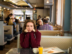 a person sitting at a table in a restaurant: Lena Dunham as the incorrigible Hannah Horvath in HBO's GirlsHBO
