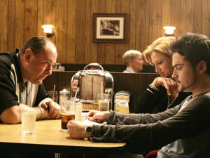 a man sitting at a table: Don't stop believing: Tony (James Gandolfini), Carmela (Edie Falco) and AJ (Robert Iler) enjoy a final family dinnerRex, HBO