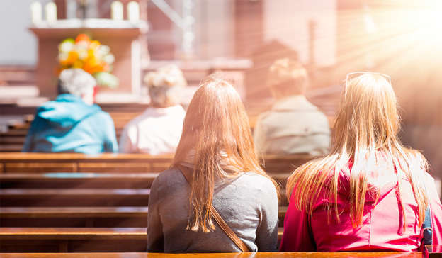a woman sitting on a bench: Churches can remain open, but only for private prayer and funerals with limited numbers. Pic: Shutterstock