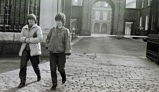 a man and a woman walking down a sidewalk: Joanne Hayes with her sister Kathleen arriving for the hearing at the Kerry Babies Tribunal in 1985. Pic: Eamonn Farrell/RollingNews.ie