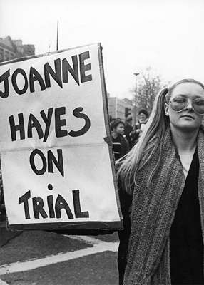 a man and a woman standing in front of a sign: A woman protests during the Kerry Babies Tribunal. Pic: RollingNews.ie