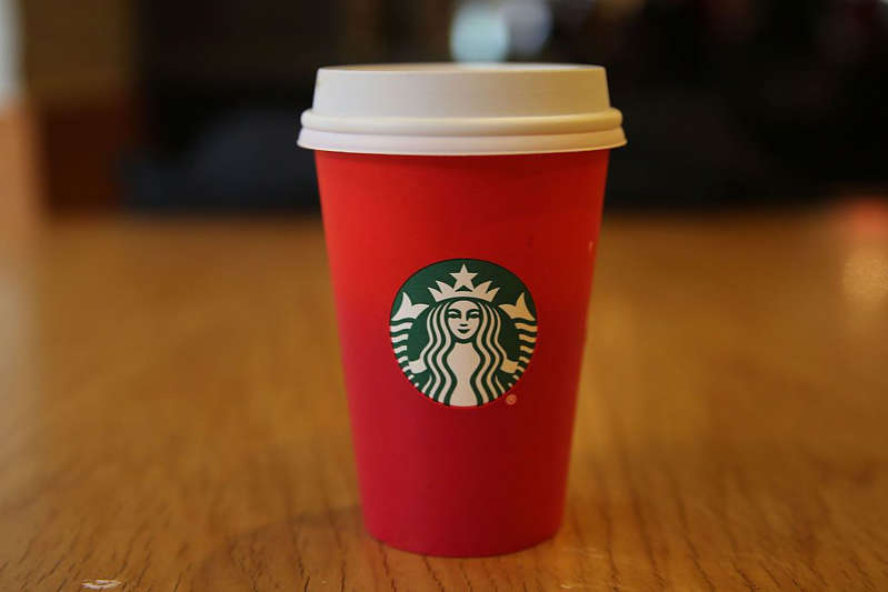 a cup of coffee sitting on top of a wooden table: Is Starbucks Open on Christmas Day 2019