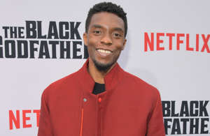 Chadwick Boseman holding a sign posing for the camera