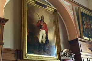 a person standing in front of a mirror posing for the camera: A portrait of Sir Thomas Picton inside the Guildhall in the centre of Carmarthen