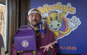 Kevin Smith holding a sign posing for the camera: Kevin Smith holding a Mooby's container.