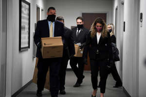 a man wearing a suit and tie: FBI Agents leave with items from Kent Calfee's office heading to Glen Casada's office next at the Cordell Hull State Office Building in Nashville, Tenn., Friday, Jan. 8, 2021. It's unknown what they are searching for.