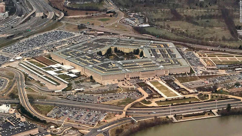 a train on a train track with buildings in the background with The Pentagon in the background