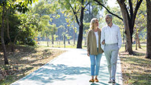 a person standing next to a tree: Older couple walking together in a park.