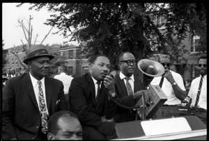 Martin Luther King, Jr. et al. standing next to a man in a suit and tie: Martin Luther King Jr. speaks during a voter registration rally in Louisville on Aug. 2, 1967.