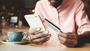 a person is using the cell phone: Man paying credit card with balance transfer credit card