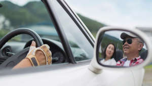 a side view mirror of a car: An older Asian couple enjoying a nice drive (you can see their smiling faces reflected in the sideview mirror)