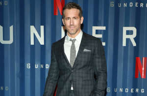 Ryan Reynolds in a suit standing in front of a building