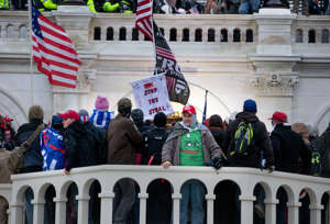 a group of people standing in front of a building: A Trump supporter wearing a T-shirt featuring Pepe the Frog, which has been appropriated as a racist hate symbol, stands outside the Capitol during a siege on Jan. 6. (Evelyn Hockstein for The Washington Post)
