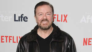 Ricky Gervais holding a sign