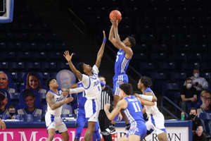 a group of men playing a game on the court: Memphis' Landers Nolley II shoots over a Tulsa defender during Sunday's loss at the Reynolds Center.