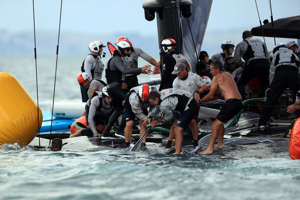 Sailors and recuers lift the capsized New York Yacht Club American Magic after Round Robin two, Race three against Luna Rossa Prada Pirelli of the Prada Cup 2021, the  challengers series of the 36th America's Cup in Auckland on January 17, 2021.