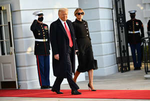 Donald Trump wearing a suit and tie standing in front of a building: President Donald Trump and First Lady Melania make their way to board Marine One before departing from the South Lawn of the White House in Washington, DC on Jan. 20, 2021.