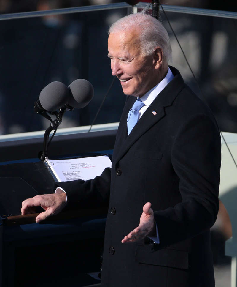 Joe Biden wearing a suit and tie: President Joe Biden gestures to stage members before delivering his inaugural address during the 2021 Presidential Inauguration of President Joe Biden and Vice President Kamala Harris at the U.S. Capitol.