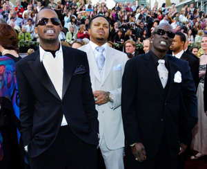 Juicy J, DJ Paul standing in front of a crowd posing for the camera: The Memphis rap group Three 6 Mafia arrives for the 78th Academy Awards in 2006.