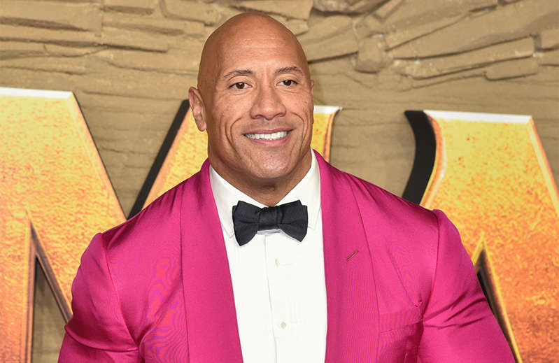 Dwayne Johnson wearing a suit and tie smiling at the camera