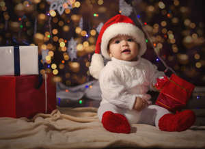 a teddy bear sitting on top of a bed: It's rapidly approaching that time of year again, and what better way to warm the spirits than to see a bunch of cute babies dressed in silly Christmas outfits!This is what it's all about. Check out our gallery to see the most adorable faces of the holiday season!