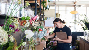 a person sitting at a table with a vase of flowers: Small-business-coronavirus