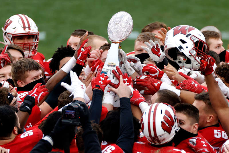 a group of baseball players playing a football game: The Wisconsin Badgers celebrate their victory over the Wake Forest Demon Deacons after winning the Duke's Mayo Bowl in Charlotte Wednesday afternoon.