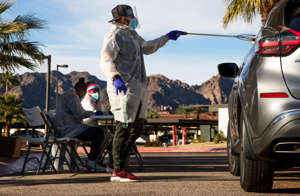 a group of people riding on the back of a car: Curative test specialist Troy Roberts gives a motorist a self-administered COVID-19 test kit outside the La Quinta Wellness Center in La Quinta, Calif., on December 30, 2020.