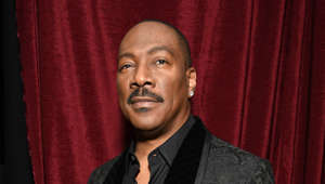 Eddie Murphy wearing a suit and tie in front of a curtain: Eddie Murphy will reprise his role as Prince Akeem Joffer following the 1988 comedy. The film follows Akeem as he must travel back to America after he discovers he has a son he never knew about. It was initially meant to be released in August 2020 but was postponed due to the pandemic and is now set for digital release in March.