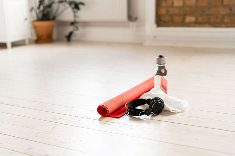 A red yoga mat on white hardwood floor in a domestic living room at home. Ready to be used in some home exercises.