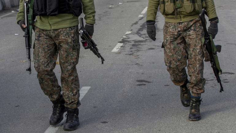 a person standing in a parking lot: Encounter in Pulwama: 3 militants trapped, operation underway in J&K