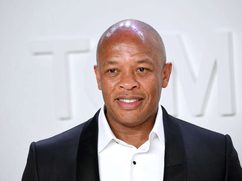 Dr. Dre wearing a suit and tie smiling at the camera: Mike Coppola / Getty Images