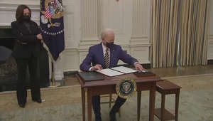 a man and a woman standing in front of a table: Biden signs executive orders on virus aid for food, unemployment