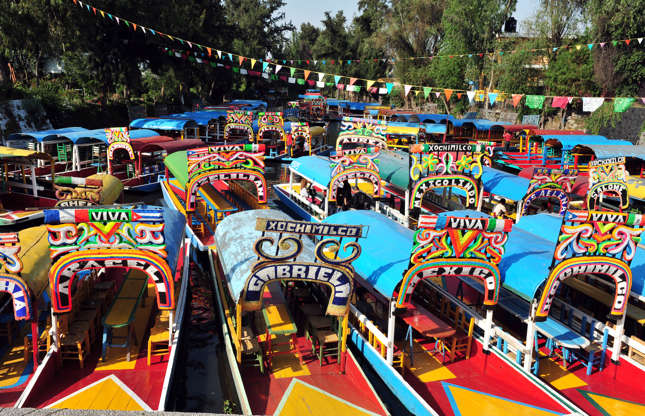 Slide 21 of 21: The Xochimilco Canals, which criss-cross Mexico City, offer another way to experience the metropolis. Visitors can board colourful gondolas, called trajineras, to tour the canals and enjoy entertaining mariachi bands, merchants, and food boats.