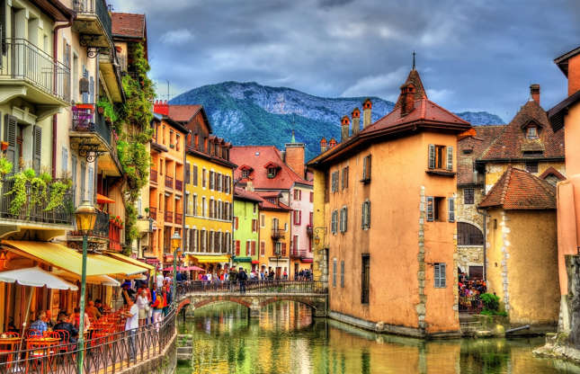 Slide 14 of 21: The canals running through this small city in the Alps lead to the blue-green waters of Lake Annecy, known as Europe's purest lake. Surrounded by majestic mountainous landscapes, Annecy boasts a medieval charm reminiscent of Venice.