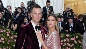 Tom Brady, Gisele Bundchen standing in front of a crowd posing for the camera