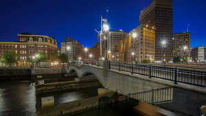 a bridge over a body of water with a city in the background: Provident, Rhode Island downtown at evening