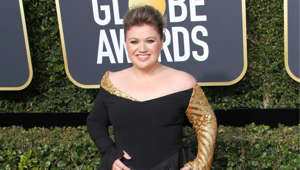 Kelly Clarkson standing in front of a sign