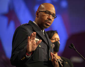 a man wearing glasses talking on a stage: Acting D.C. police chief Robert J. Contee III addresses reporters at a public safety briefing on Jan. 15.