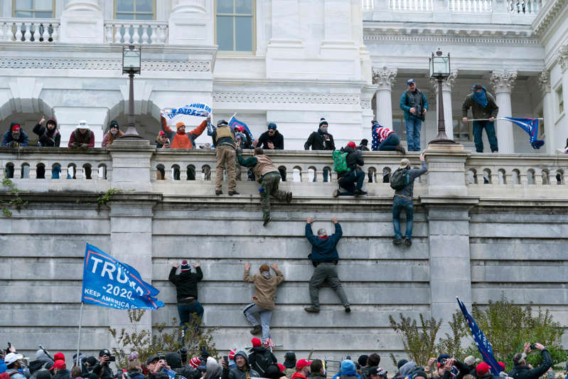 a group of people walking in front of a building: In this Wednesday, Jan. 6, 2021 file photo, supporters of President Donald Trump scale the west wall of the the U.S. Capitol in Washington.