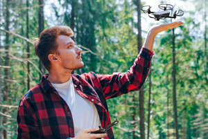 a man standing next to a forest: Drone With Camera Amazon